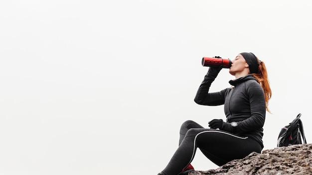 Herbstlauf im freien training und trinken aus der thermoskanne