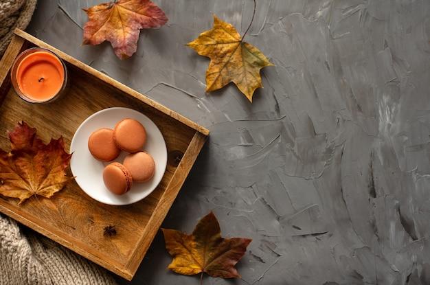 Herbstlayout braune makronen auf einem tablett mit abgefallenen blättern und aromakerzen auf grauem hintergrund