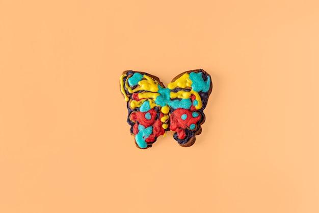 Herbstlayout, komposition mit lebkuchen. lebkuchen in form eines schmetterlings wird vom kind bemalt. kinderkreativität und diy, mach es selbst
