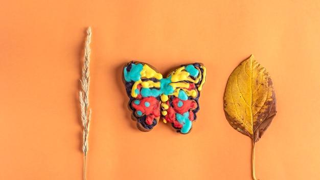 Herbstlayout, komposition mit lebkuchen und herbstblättern. lebkuchen in form eines schmetterlings wird vom kind bemalt. kinderkreativität und diy, mach es selbst