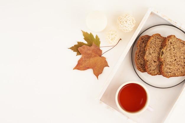 Herbstlebensmittelscheiben bananenbrot, eine tasse tee, trockene blätter, weißer holztisch.