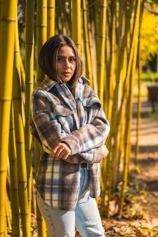 Herbstlebensstil, junges kaukasisches brünettes mädchen in einem karierten wollpullover in einem bambuswald