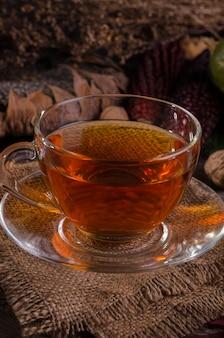 Herbstlich gemütliches stillleben mit glasteekanne und tasse tee auf einer sackleinen-serviette