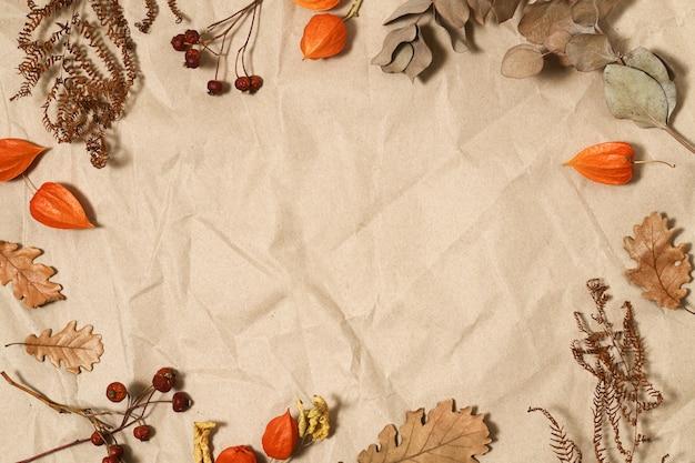 Herbstliche blätter und beeren auf braunem papier