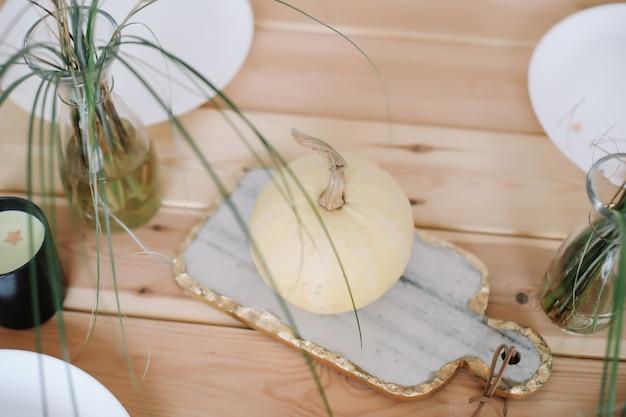 Herbstliche festliche tischdekoration mit weißen kürbisplatten und kerzen auf holztisch-draufsicht