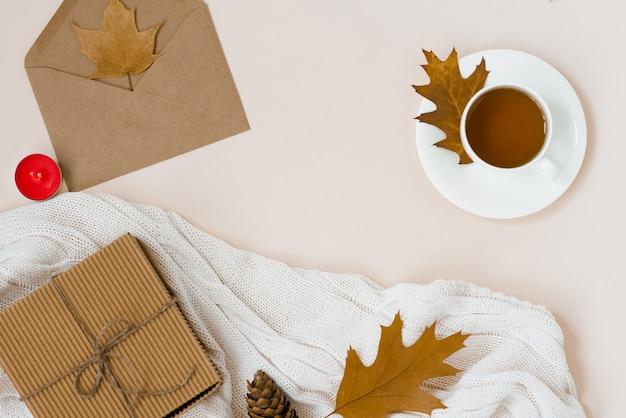 Herbstliche flache lage mit weißem gestricktem plaid, heißer tasse tee und gefallenen braunen blättern, krabbenumschlag, geschenkbox.
