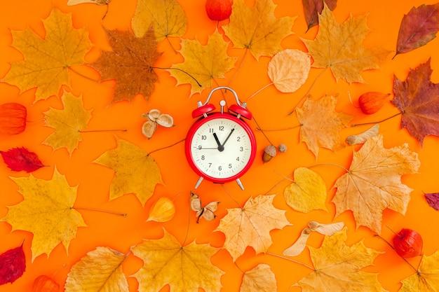 Herbstliche flache laienkomposition mit rotem wecker und trockenen blättern