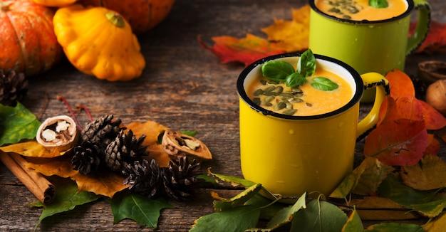 Herbstliche kürbissuppe mit kürbiskernen im blechbecher, thanksgiving, rustikaler stil