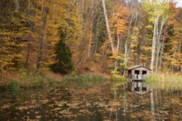 Herbstliche ländliche landschaft - herbst eichen in der nähe des teiches und einsames kleines haus