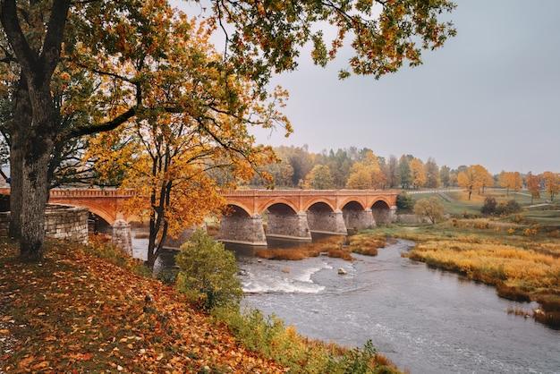 Herbstliche landschaft. die alte backsteinbrücke über den fluss venta in kuldiga, lettland.