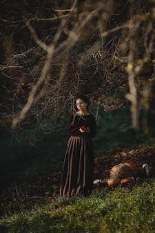 Herbstliche stimmung. gothic style. brunettefrau im dunkelroten tuch