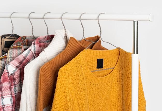 Herbstliche vintage-kleidung hängt auf kleiderbügeln am regal. beige trenchcoat, pullover, karierte hemden. raumorganisation, winterreinigung. modell, vorlage