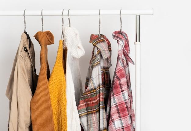 Herbstliche vintage-kleidung hängt auf kleiderbügeln am regal. beige trenchcoat, pullover, karierte hemden. raumorganisation, winterreinigung