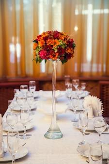 Herbstlicher blumenstrauß schmückt den festlichen tisch im restaurant.