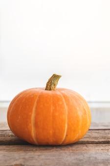 Herbstlicher hintergrund. natürlicher herbstfallansichtkürbis auf hölzernem hintergrund. inspirierende oktober- oder september-tapete. wechsel der jahreszeiten, reifes bio-lebensmittelkonzept. halloween-party thanksgiving day
