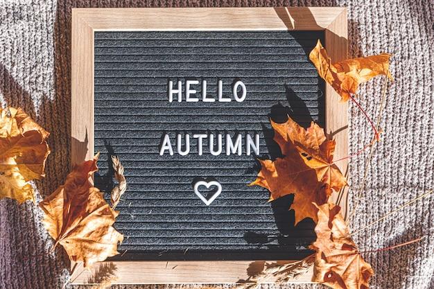 Herbstlicher hintergrund. schwarzes briefbrett mit textphrase hallo herbst und getrockneten blättern, die auf weißem strickpullover liegen. ansicht von oben, flach. thanksgiving-banner. hygge stimmung kaltwetterkonzept