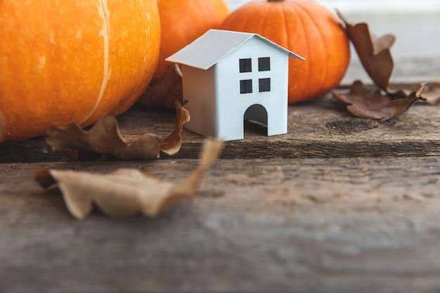 Herbstlicher hintergrund. spielzeughaus und kürbis auf hölzernem hintergrund. thanksgiving-banner-kopienraum. hygge-stimmung, jahreszeitenwechsel-konzept. hallo herbst mit familien-halloween-party.