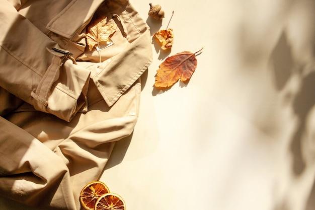 Herbstlicher trenchcoat mit herbstlaub und kontrastierenden schatten. damenmode