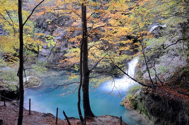 Herbstliches bild eines wasserfalls im urederra fluss