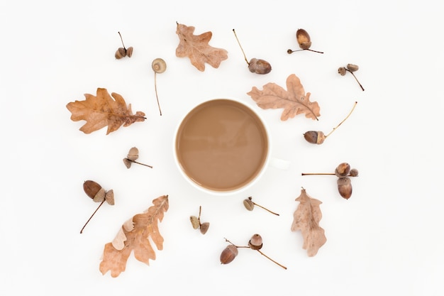 Herbstliches blasses muster, blätter, eicheln und tasse kaffee auf weiß