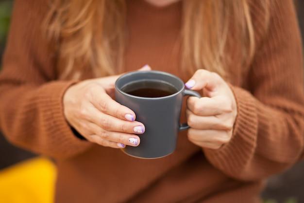 Herbstliches picknick im freien. junge frau, die tasse heißen kaffees in einer hand hält.