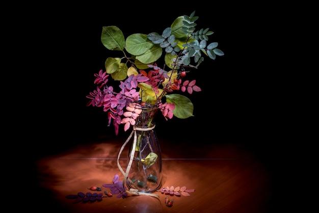 Herbstliches stillleben. blumenstrauß in einer vase auf einem schwarzen hintergrund