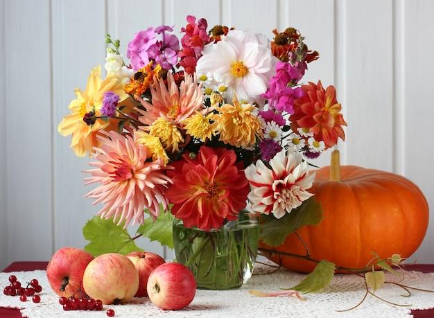 Herbstlicht stillleben mit einem blumenstrauß aus blumen, äpfeln und kürbis auf dem tisch. ernte, fülle.