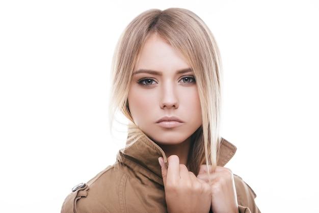 Herbstmode. attraktive junge frau im mantel, die ihren kragen justiert und in die kamera schaut, während sie vor weißem hintergrund steht