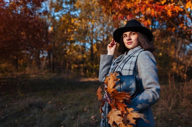 Herbstmode. junge frau, die stilvolle ausstattung trägt und draußen geldbeutel hält. kleidung und accessoires