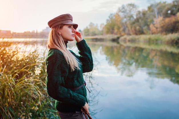 Herbstmode. junge frau, die stilvolle ausstattung und hut durch fluss trägt. kleidung und accessoires