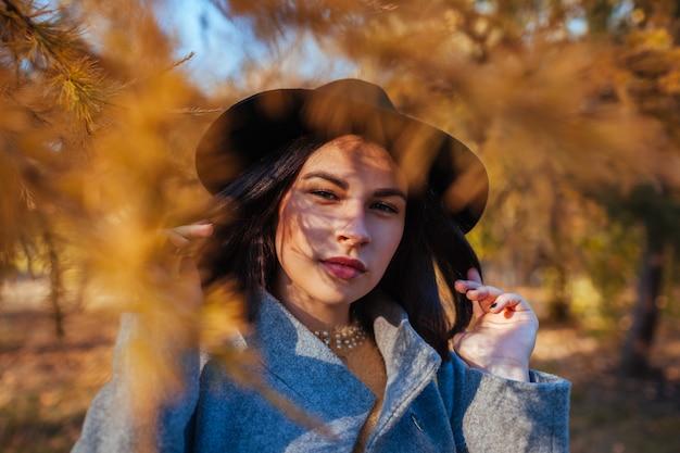 Herbstmode. porträt der jungen frau mit schatten auf dem gesicht, das draußen stilvolle ausstattung trägt. kleidung und accessoires