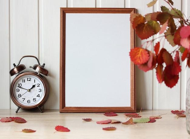Herbstmodell mit einem blumenstrauß aus blättern und einem leeren holzrahmen auf dem tisch natürlicher hintergrund im september mit einem wecker