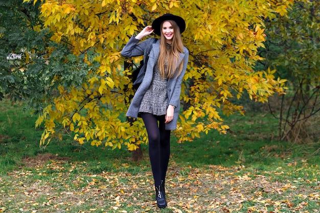 Herbstmodeporträt der eleganten glamourfrau, die im erstaunlichen stadtpark, im stilvollen mantel, im rucksack und im weinlesehut aufwirft. allein gehen, kaltes wetter
