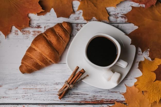 Herbstmorgen frühstücken sie mit einem tasse kaffee und einem hörnchen auf einem holztisch mit ahornblättern