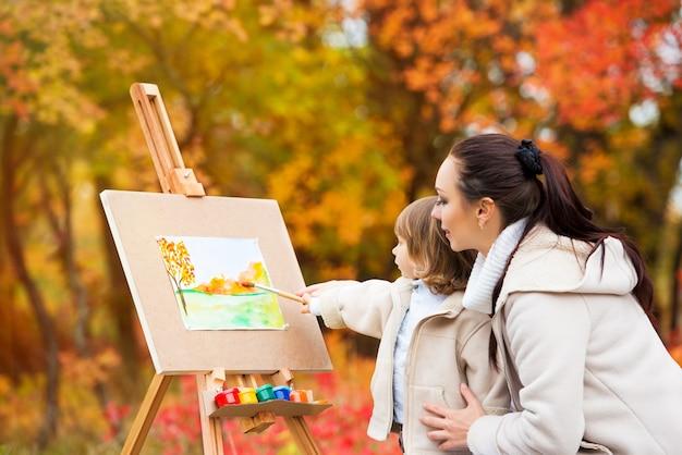 Herbstnatur, mutter und tochter malen ein bild in einem park aus herbstblättern, malen ein kleines kind, kinderkreativität.