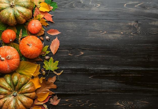 Herbstoberfläche mit den kürbisen, herbstlaub, hopfen und eicheneicheln, die auf einer schwarzen holzoberfläche liegen