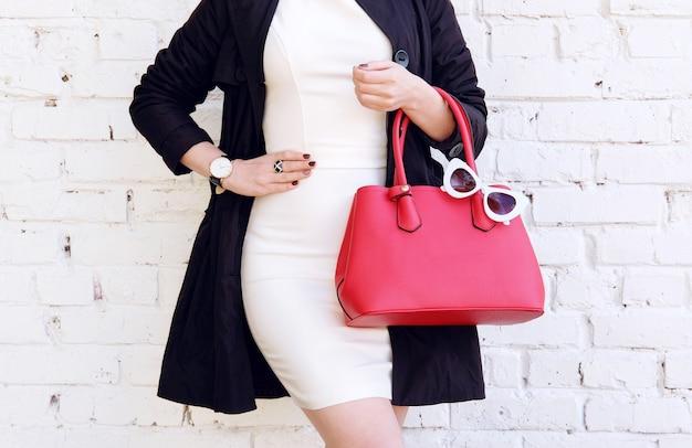 Herbstoutfit. frau im schwarzen mantel halten rote handtasche in der hand. stilvolles accessoire