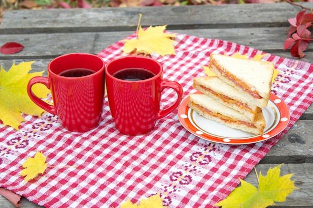 Herbstpicknick in der natur, zwei rote schalen und sandwich