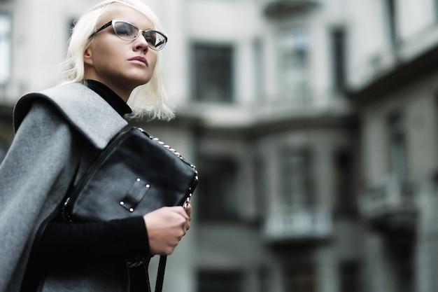 Herbstporträt der schönen blonden frau im grauen mantel mit schwarzer tasche