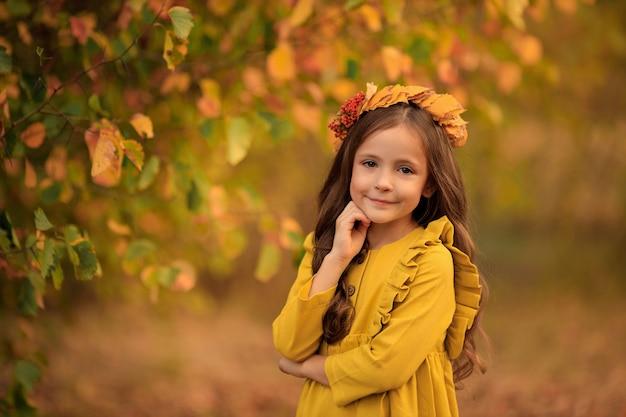 Herbstporträt eines schönen mädchens, das in den park geht, der einen kranz der gelben blätter trägt