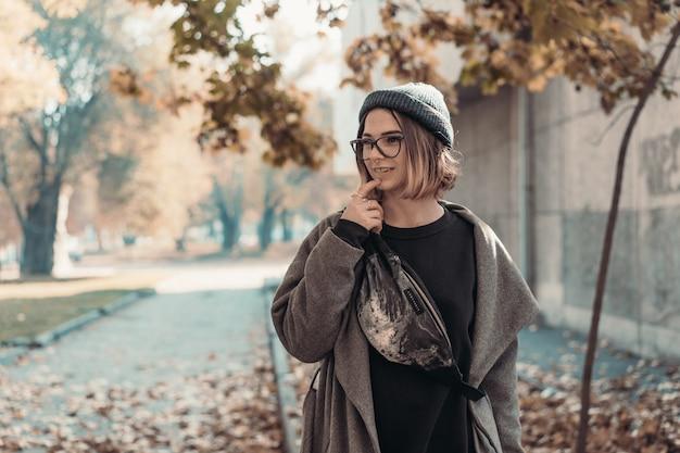 Herbstporträt im freien der jungen frau, die in der straße der europäischen stadt geht.