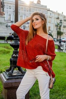 Herbstporträt von blondem hübschem weoman mit hellem make-up, orangefarbenem pullover und weißen jeans. im freien spazieren gehen.
