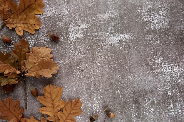 Herbstrahmen aus braunen getrockneten blättern und eicheln auf dunklem betonhintergrund. vorlage mockup herbst, halloween. flach legen, hintergrund kopieren.