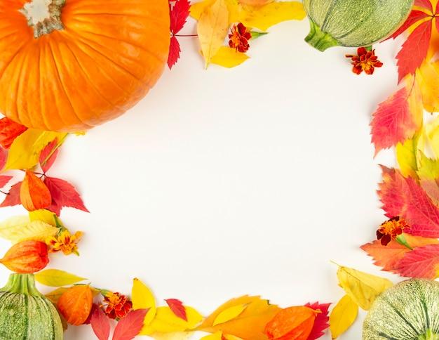 Herbstrahmen aus bunten blättern und kürbissen auf einem leuchttisch.