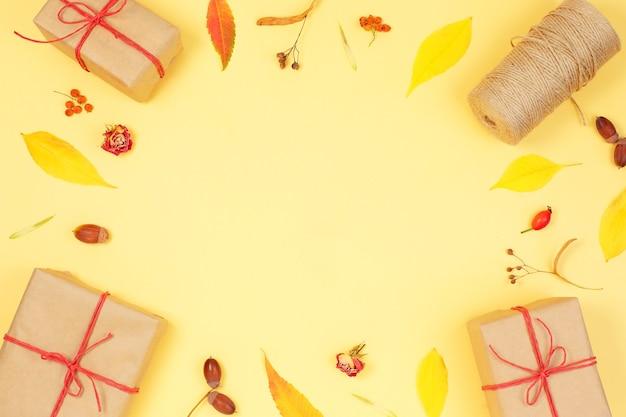 Herbstrahmen mit geschenkboxen und herbstlaub