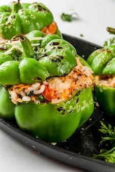 Herbstrezepte. hausgemachte gefüllte paprika mit hackfleisch, karotten, tomaten, kräutern, käse. auf weiß, in der backform,