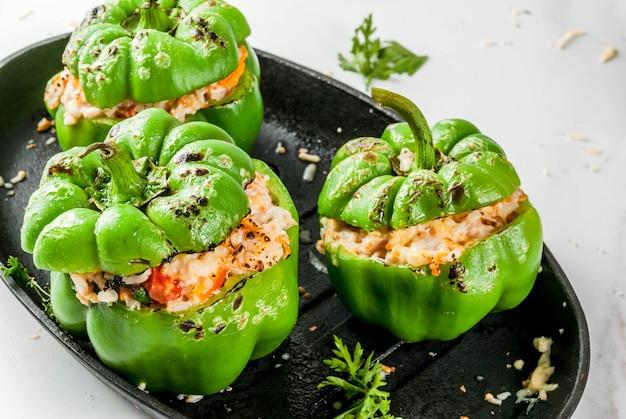 Herbstrezepte. hausgemachte gefüllte paprika mit hackfleisch, karotten, tomaten, kräutern, käse. auf weißer marmortabelle in der backform kopieren sie raum