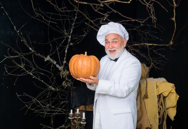 Herbstrezepte konzept glücklicher bärtiger halloweenkoch in kochmütze mit kürbis nützlichem gemüse