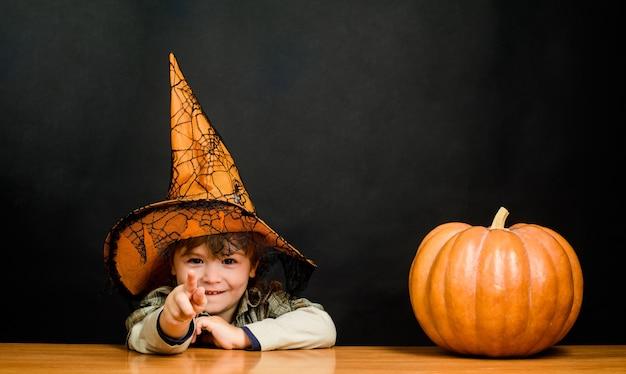 Herbstrezepte konzept thanksgiving day kochen süßer kinderjunge in hexenhut mit halloween-kürbis