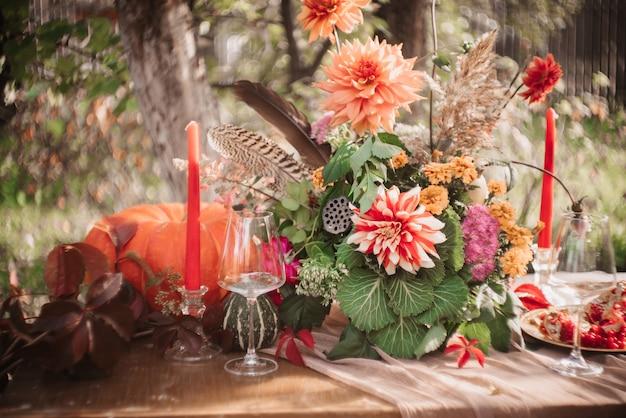 Herbstromantische dekoration: ein strauß dahlien, granatäpfel, kerzen, kürbisse und gläser